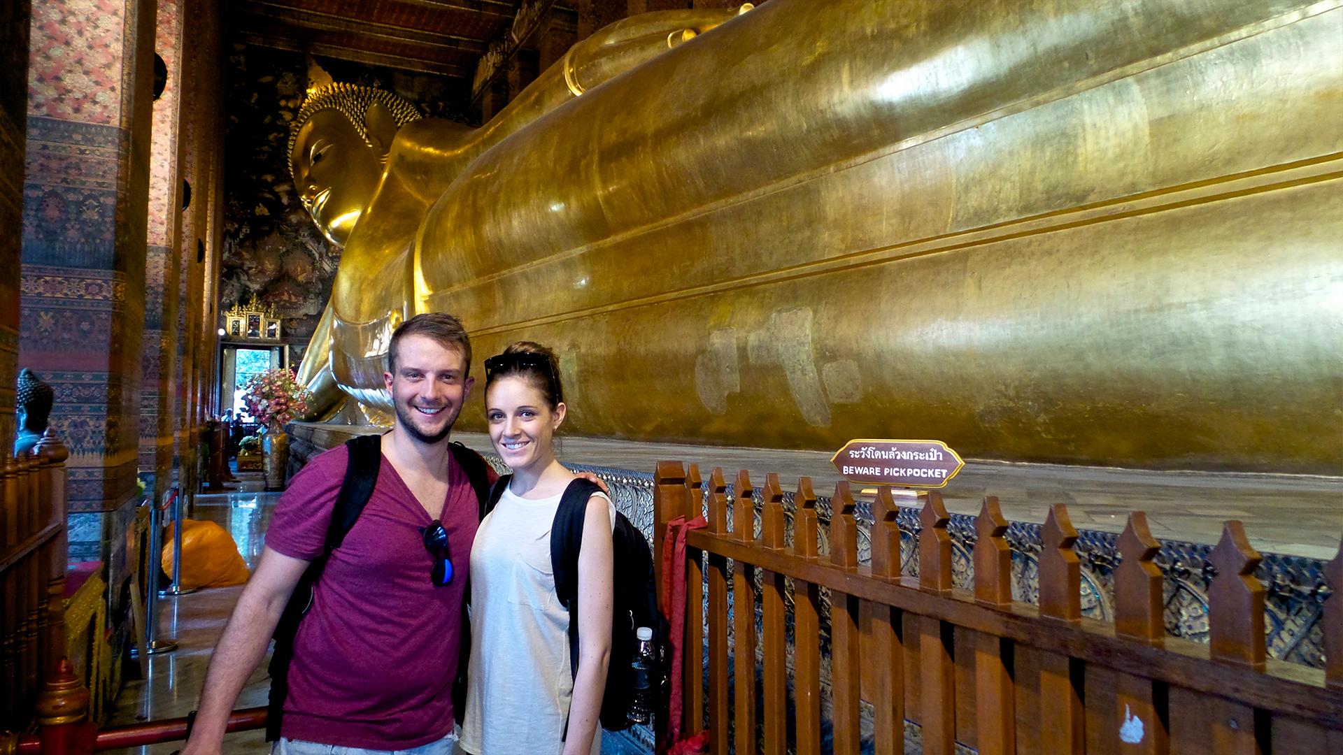 Due belli in modo assurdo davanti alla statua del buddha sdraiato